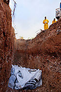 Men put the bodies of cholera victims into a mass grave on Wednesday, November 24, 2010 near Port-au-Prince, Haiti.