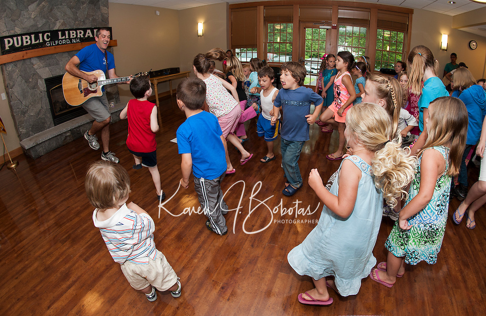"Paul Warnick starts off the ""Dream Big""  Summer Reading program at Gilford Library by getting youngsters on their feet to ""Shake Their Sillies"" out and ""Wiggle Waggle""  Monday afternoon.   (Karen Bobotas/for the Laconia Daily Sun)"