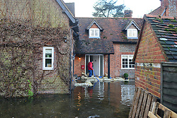 © Licensed to London News Pictures. 09/01/2014. Marlow, UK. A home owner pumps out rising ground water from his property. Rising river levels in the River Thames at Marlow in Buckinghamshire have led to flooding and property damage along the river today 9th January 2014. Large areas of Britain are experiencing flooding after wet weather. Photo credit : Stephen Simpson/LNP