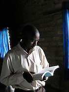 Rwanda- A Rwandan man reads by the light of the window in the school library at Gary Scheer school in the Southern Province, Rwanda.