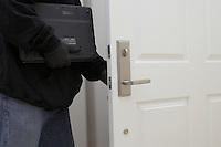 Burglar stealing laptop, mid section