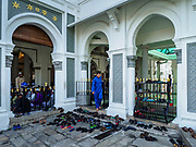 """22 AUGUST 2018 - GEORGE TOWN, PENANG, MALAYSIA:  A man leaves Kapitan Keling Mosque after services for Eid al-Adha services. It is the oldest mosque in George Town. Eid al-Adha, """"Feast of the Sacrifice"""" is the second of two Islamic holidays celebrated worldwide each year. It honors the willingness of Ibrahim (Abraham) to sacrifice his son as an act of obedience to God's command.    PHOTO BY JACK KURTZ"""