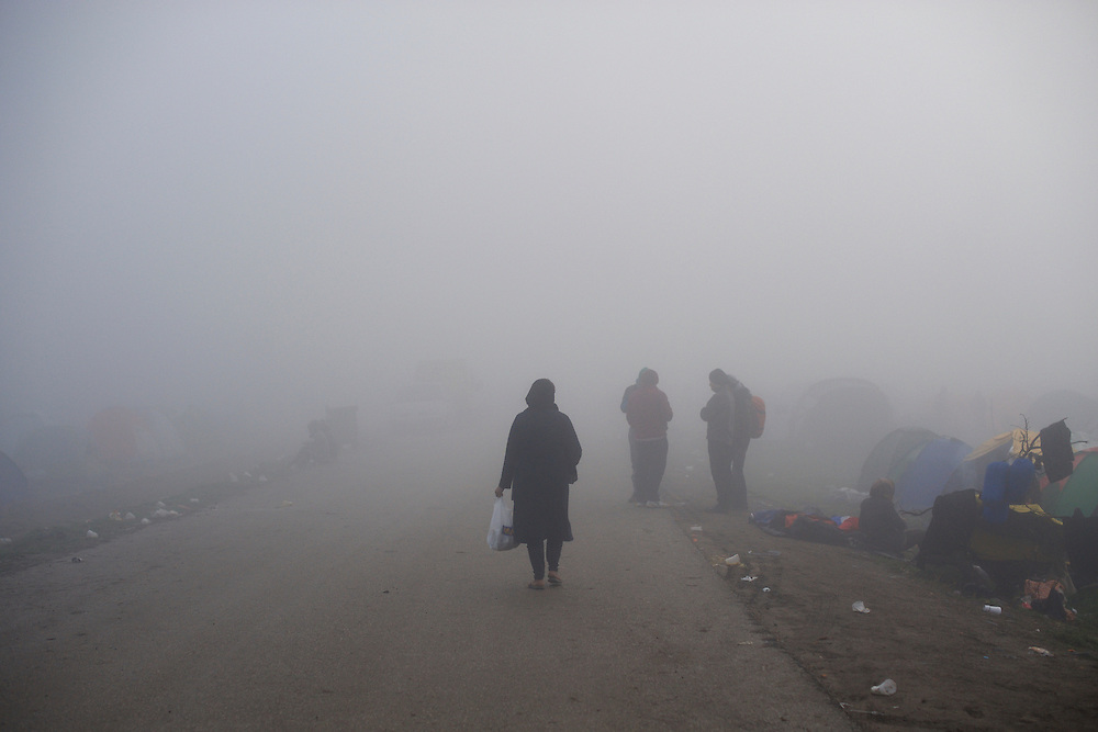 Migrants walk by the border post between Greece and Macedonia during a foggy morning in Idomeni, Greece.