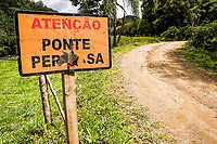 Placa de advertência em estrada de terra no distrito de Rio Natal. São Bento do Sul, Santa Catarina, Brasil. / Warning sign in a dirt road. Sao Bento do Sul, Santa Catarina, Brazil.