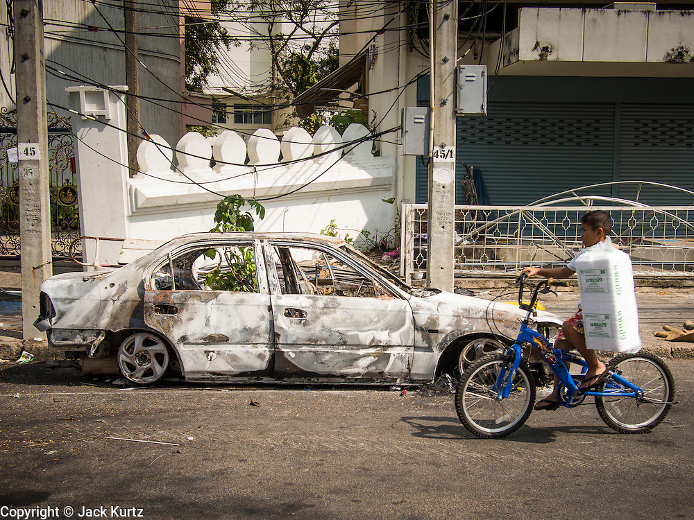 10 DECEMBER 2013 - BANGKOK, THAILAND:  A boy rides his bike past a burnt out car in the wake of anti-government protests in Bangkok. Protestors remained around Government House in Bangkok Tuesday but their mood was festive rather than angry. They listened to music and danced while protest leaders planned their next move.     PHOTO BY JACK KURTZ