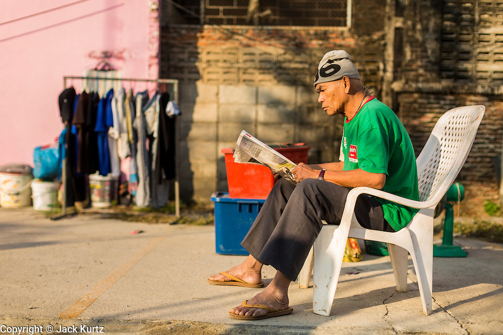 19 JANUARY 2014 - BANGKOK, THAILAND:  A member of the cast for a mor lam show reads a Thai newspaper backstage before a show in Khlong Tan Market in Bangkok. Mor Lam is a traditional Lao form of song in Laos and Isan (northeast Thailand). It is sometimes compared to American country music, song usually revolve around unrequited love, mor lam and the complexities of rural life. Mor Lam shows are an important part of festivals and fairs in rural Thailand. Mor lam has become very popular in Isan migrant communities in Bangkok. Once performed by bands and singers, live performances are now spectacles, involving several singers, a dance troupe and comedians. The dancers (or hang khreuang) in particular often wear fancy costumes, and singers go through several costume changes in the course of a performance. Prathom Bunteung Silp is one of the best known Mor Lam troupes in Thailand with more than 250 performers and a total crew of almost 300 people. The troupe has been performing for more 55 years. It forms every August and performs through June then breaks for the rainy season.              PHOTO BY JACK KURTZ