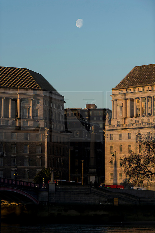 © Licensed to London News Pictures. 28/01/2016. London, UK. The moon still visible as warm orange sunshine is cast over Westminster on a clear day at sunrise in London on a cold winter morning. Photo credit: Ben Cawthra/LNP