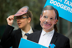 © licensed to London News Pictures. London, UK 24/04/2014. Protesters wearing masks featuring the face of Barclays boss Antony Jenkins protest against Barclays helping businesses set up in tax havens, during Barclays Annual General Meeting (AGM) outside Royal Festival Hall in London. Photo credit: Tolga Akmen/LNP
