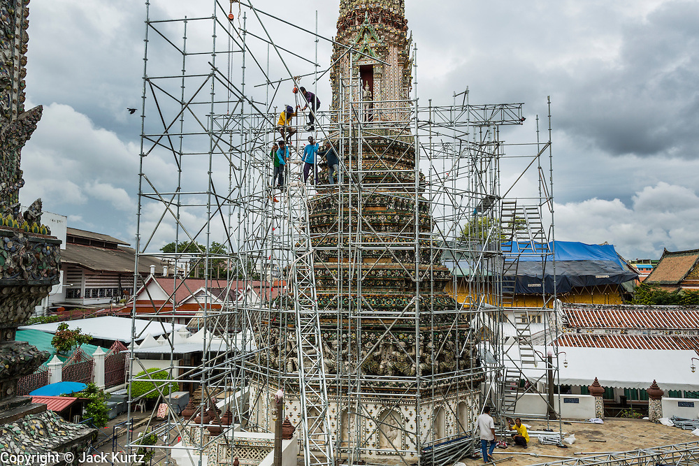 """23 SEPTEMBER 2013 - BANGKOK, THAILAND:  Workers put up scaffolding around a chedi at Wat Arun in Bangkok. The full name of the temple is Wat Arunratchawararam Ratchaworamahavihara. The outstanding feature of Wat Arun is its central prang (Khmer-style tower). The world-famous stupa, known locally as Phra Prang Wat Arun, will be closed for three years to undergo repairs and renovation along with other structures in the temple compound. This will be the biggest repair and renovation work on the stupa in the last 14 years. In the past, even while large-scale work was being done, the stupa used to remain open to tourists. It may be named """"Temple of the Dawn"""" because the first light of morning reflects off the surface of the temple with a pearly iridescence. The height is reported by different sources as between 66,80 meters and 86 meters. The corners are marked by 4 smaller satellite prangs. The temple was built in the days of Thailand's ancient capital of Ayutthaya and originally known as Wat Makok (The Olive Temple). King Rama IV gave the temple the present name Wat Arunratchawararam. Wat Arun officially ordained its first westerner, an American, in 2005. The central prang symbolizes Mount Meru of the Indian cosmology. The temple's distinctive silhouette is the logo of the Tourism Authority of Thailand.          PHOTO BY JACK KURTZ"""