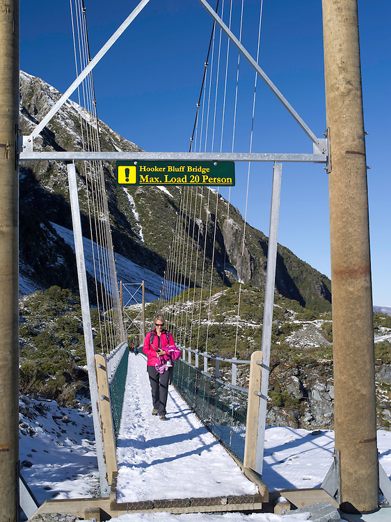 A woman tramps across the Hooker Bluff Suspension Bridge on her way to the Hooker Valley; Aoraki/Mt. Cook National Park, New Zealand.
