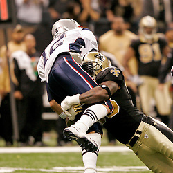 2009 November 30:  New England Patriots quarterback Tom Brady (12) is hit by New Orleans Saints defensive end Bobby McCray (93) as he throws during a 38-17 win by the New Orleans Saints over the New England Patriots at the Louisiana Superdome in New Orleans, Louisiana.