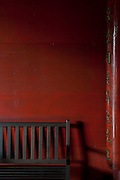 Mauritius. Bench, red wall and pillar with caligraphy. Port Louis.