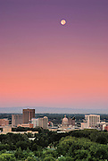 Idaho, Boise.  Colorful downtown skyline shot with moon overhead in summer.