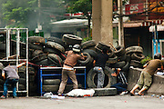16 MAY 2010 - BANGKOK, THAILAND: Anti government protesters on Rama IV Road take cover behind barricades and look for unidentified snipers opening fire on them Sunday. Thai troops and anti government protesters clashed on Rama IV Road again Sunday afternoon in a series of running battles. Troops fired into the air and unidentified snipers shot at pedestrians on the sidewalks. At one point Sunday the government said it was going to impose a curfew only to rescind the announcement hours later. The situation in Bangkok continues to deteriorate as protests spread beyond the area of the Red Shirts stage at Ratchaprasong Intersection. Many protests now involve people who have not been active in the Red Shirt protests and live in the vicinity of Khlong Toei slum and Rama IV Road. Red Shirt leaders have called for a cease fire, but the government indicated that it is going to go ahead with operations to isolate the Red Shirt camp and clear the streets.      PHOTO BY JACK KURTZ