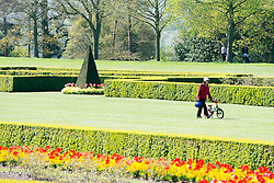 © Licensed to London News Pictures. 16/04/2014. Cliveden, UK. A woman walks a childs bike through the Parterre with its vibrant floral displays.  People enjoy the sunshine at Cliveden in Buckinghamshire today 16th April 2014. Photo credit : Stephen Simpson/LNP