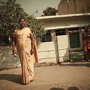 Devo Bagel (48) next to her rented home in Raipur, with her visiting daughet, and her husband. She used to live in a slum but thanks to the loan she took, she now rents a bigger and more comrtable home where she also cooks for the evening work.