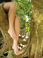 Young woman sitting on tree branch close-up on legs