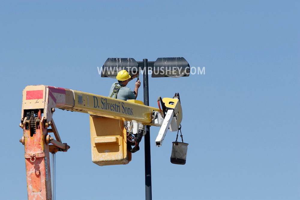 Town of Wallkill, NY - A worker in a bucket truck repairs a light at the top of a tower in a mall parking lot on Sept. 25, 2009.