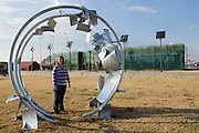 "Greensburg, Kansas, USA..Executive Director Stacey Barnes in front of 5.4.7 Art Center (sculpture by Jim Gallucci)..The 5.4.7 Arts Center takes their name from the date of the tornado that devastated Greensburg on May 4, 2007. It is the first LEED Platinum building designed and constructed by students, and is the first LEED Platinum certified structure in the state of Kansas. The building earned the LEED Platinum certification through its use of wind turbines, photovoltaic panels, geothermal climate control, recycled building materials and a host of other ecologically minded features. The 5.4.7 Art Center is a community arts center to raise awareness of fine arts, both visual and performing, making arts accessible to everyone and provide an environment to create and gather knowledge through classes, exhibits and performances. ""The arts are extremely important to our community in order to maintain and cultivate our identity, our heritage, and our culture.""..""Greensburg: Better, Stronger, Greener!"".On May 4, 2007, an EF5 tornado cut a 1.7-mile path of destruction through Greensburg, Kansas. Winds reaching speeds of 205 miles per hour uprooted trees, demolished homes and leveled the town. Eleven people died and 95% of the buildings were destroyed beyond repair. Residents have since worked furiously to rebuild it in a way that is both economically and environmentally sustainable and to meet the highest environmental standards. Greensburg, whose population has dropped from about 1400 to 800 following the storm and is now growing again, is currently the greenest town in America and the first in the United States to pass a resolution to certify that all city-owned buildings earn LEED Platinum accreditation, the highest level of the LEED rating system...Foto © Stefan Falke"