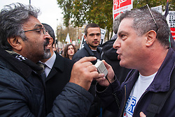 Downing Street, London, November 15th 2014. Dozens of Palestinians and their supporters faced a small group of Israeli counter protesters as they demonstrated outside the gates of Downing Street against Israel. Police had to intervene as several from both sides took exception to what was being said, with the half-dozen-strong Israeli group eventually moving off. Pictured: A Palestinian protester, left, and a pro Israel counter protester exchange accusations as tensions rise.