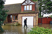 © Licensed to London News Pictures. 09/02/2014. Wraysbury, UK. A man leaves his property to survey any damage. Flooding in Wraysbury in Berkshire today 9th February 2014 after the River Thames burst its banks. Photo credit : Stephen Simpson/LNP