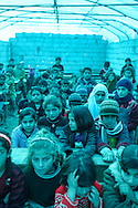 Syrian school children at a makeshift school under a blue tarp at the camp for displaced Syrians in Atmeh, Syria.