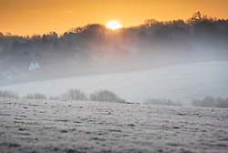 © Licensed to London News Pictures. 02/12/2019. Epsom, UK. The sun rises over a frozen Epsom Downs. A cold start for some parts of the south with temperatures just below freezing at dawn. Photo credit: Peter Macdiarmid/LNP