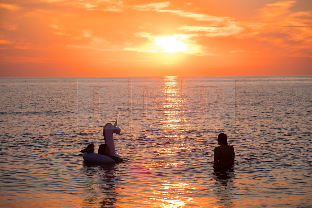 © Licenced to London News Pictures. Aberystwyth Wales UK, Thursday 26 July 2018. UK Weather: Two young women swimming with an inflatable unicorn are  silhouetted by the setting sun over the sea in Aberystwyth at the end of a day of record breaking hot summer sunshine.  The UK wide heatwave continues, with little real respite from the very dry weather  despite some rain in the forecast for the weekend. Photo credit: Keith Morris/LNP