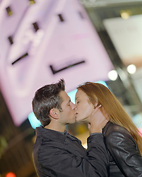 beautiful couple kissing at night surrounded by city lights in New York City