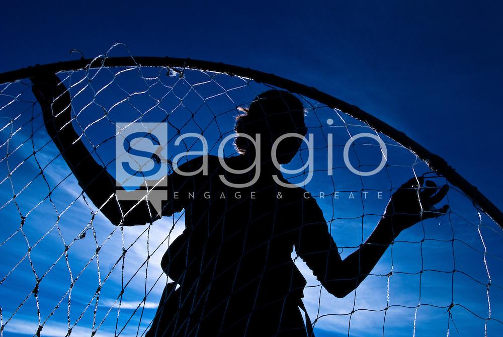 A woman fixes the netting on a dipnet on the Kenai Peninsula, Alaska.