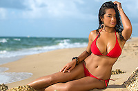 Portrait of hot female in red bikini sunbathing over the blurred beach background
