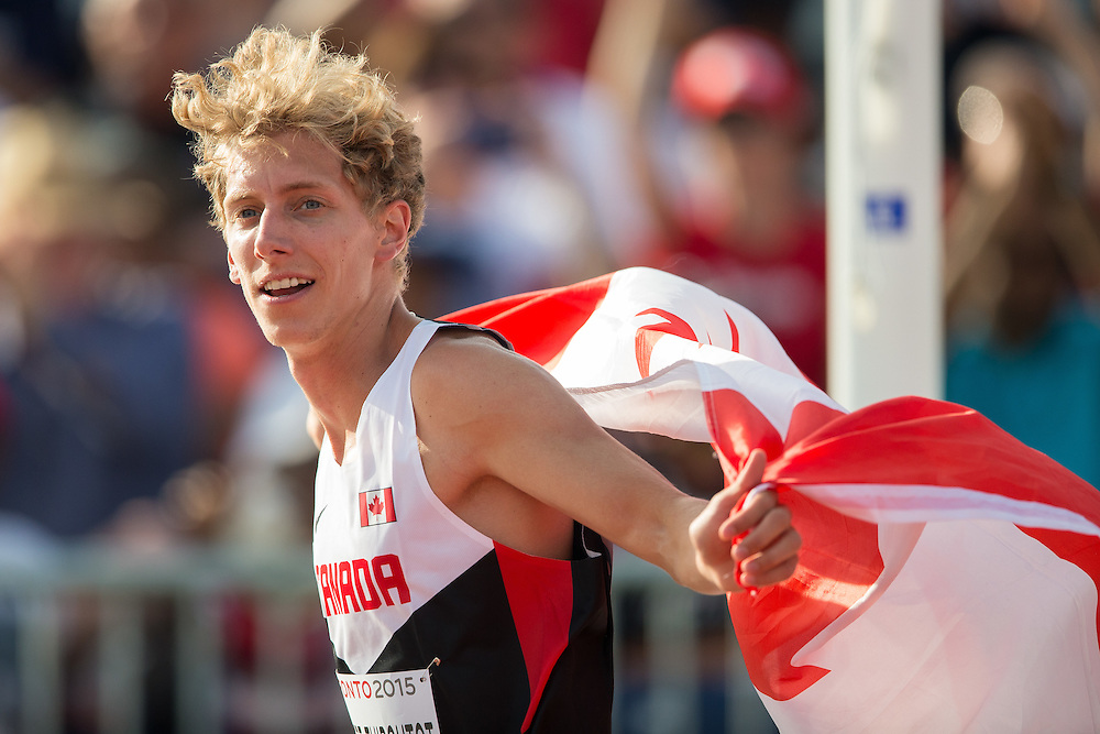 Charles Philbert-Thiboutot of Canada celebrates with the Canadian flag following his bronze medal win in the men's 1500 metres at the 2015 Pan American Games at CIBC Athletics Stadium in Toronto, Canada, July 24,  2015.  AFP PHOTO/GEOFF ROBINS