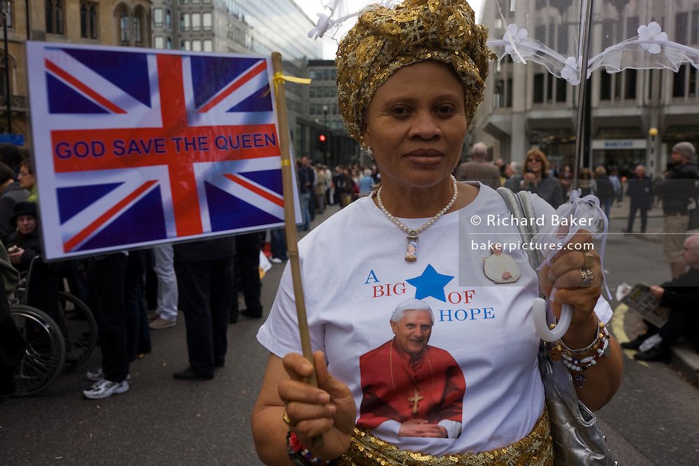 Pro-Papal supporters party in front of Westminster Abbey in London during Pope Benedict XVI's papal tour of Britain 2010, the first visit by a pontiff since 1982. Taxpayers footed the £10m bill for non-religious elements, which largely angered a nation still reeling from the financial crisis. Pope Benedict XVI is the head of the biggest Christian denomination in the world, some one billion Roman Catholics, or one in six people. In Britain there are about five million Catholics but only a quarter of Catholics regularly attend Sunday Mass and some churches have closed owing to spending cuts.