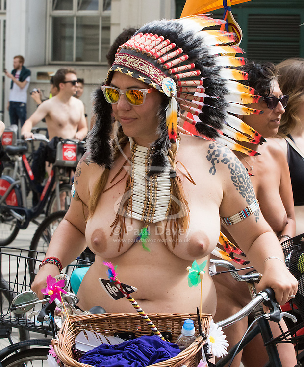 Westminster Bridge, London, June 11th 2016. Hundreds of naked and semi-naked cyclists participate in the World Naked Bike Ride that takes place in cities around the world, to highlight the alternatives to hydrocarbon fuels. PICTURED: A woman wears a Native American headress.