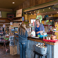 A woman buys milk at the Blue Raeven Farmstand in the heart of Oregon's wine country in the town of Amity.