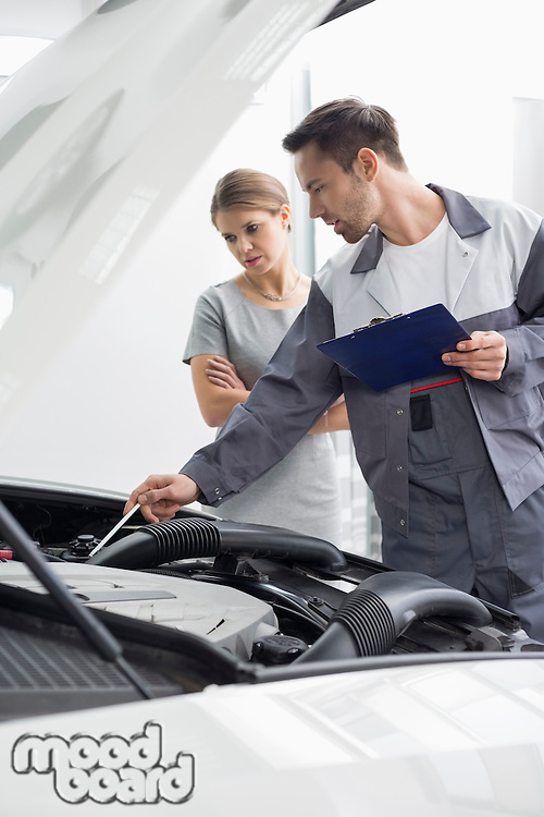 Male maintenance engineer explaining car engine to female customer in repair shop