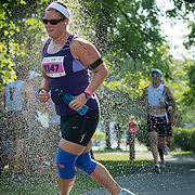 A triathlete quickly refreshes herself under a shower by a surprisingly hot late summer day.