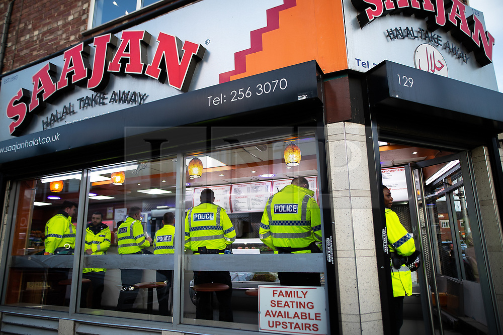 © Licensed to London News Pictures. 15/06/2018. Manchester, UK. Police queue for a takeaway . People celebrate Eid-ul-Fitr , the end of a month of fasting during Ramadan , in Rusholme in Manchester . Photo credit: Joel Goodman/LNP