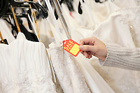 Cropped shot of female hands holding price tag attached to wedding gown in bridal boutique