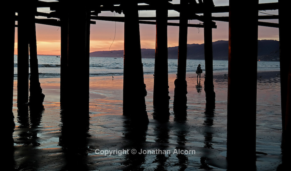 Santa Monica beach is seen through pylons underneath the Santa Monica Pier