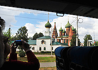 """Inbound from Uglich, tourists on a bus take photographs of one of Yaroslavl's many churches. Established in 1010, this important """"Golden Ring"""" Russian city is located at the confluence of the Volga and the Kotorosl Rivers. The historic city center, home to many landmark buildings, has been designated a UNESCO World Heritage Site."""