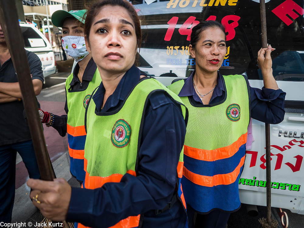 18 AUGUST 2015 - BANGKOK, THAILAND: Women who work as street sweepers for the city of Bangkok look at Erawan Shrine before cleaning the area. An explosion at Erawan Shrine, a popular tourist attraction and important religious shrine in the heart of the Bangkok shopping district, killed at least 20 people and injured more than 120 others, including foreign tourists, during the Monday evening rush hour. Twelve of the dead were killed at the scene. Thai police said an Improvised Explosive Device (IED) was detonated at 18.55. Police said the bomb was made of more than six pounds of explosives stuffed in a pipe and wrapped with white cloth. Its destructive radius was estimated at 100 meters.    PHOTO BY JACK KURTZ
