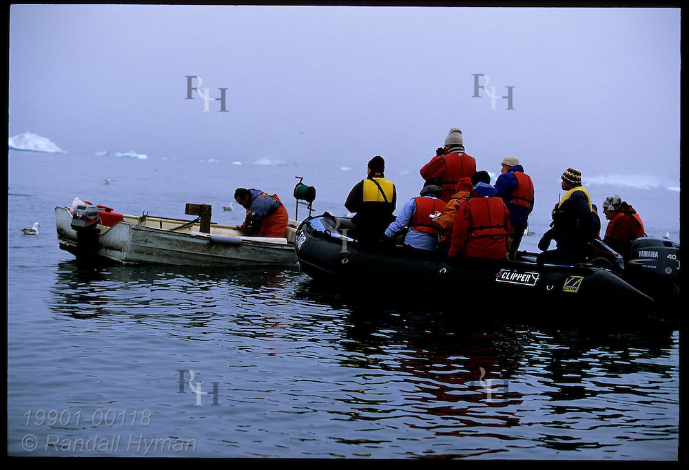 Tourists in rubber raft watch Greenlandic fisherman work in his boat in Disko Bay near Ilulissat, Greenland