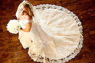 Bridal picture taken in white wedding dress from above against beautiful dark hardwood floors.