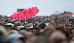 © licensed to London News Pictures . 30/06/2012 . Manchester , UK . A single , tatty , pink umbrella is held up by someone in the crowd during a performance by Beady Eye at Heaton Park . The band perform as warm up for the Stone Roses , who are on their comeback tour . Photo credit : Joel Goodman/LNP