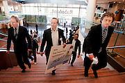 Bart Combée (midden) van de Consumentenbond loopt samen met dhr. Op den Brouw van de Rabobank (links) door het hoofdkantoor van de Rabobank in Utrecht. De Consumentenbond overhandigt aan de grootste hypotheekverstrekker van Nederland een petitie met ruim 5000 handtekeningen waarin wordt gevraagd de hypotheekrente te verlagen. Volgens de bond is de hypotheekrente die de banken rekenen gemiddeld een procent te hoog. De Rabobank spreekt dat tegen.<br /> <br /> The consumer union Bart Combée (center) of the Consumentenbond (an organisation for the consumers) is walking with Op den Brouw (left) of the Rabobank at the headquarters of the bank. Combée will hand over a petition to demand better rates for the mortgages.