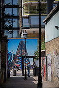 Young women talk in an graffiti alleyway opposite a construction hoarding showing the Foster-designed Principal Tower that's under construction on Shoreditch High Street, on 10th May 2017, in London, England.