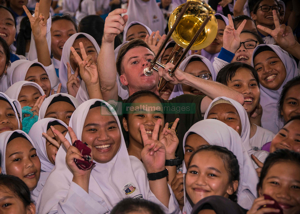 180816-N-FV739-0148 SIPITANG, Malaysia (Aug. 16, 2018) Sgt. Colin Deeter plays his instrument in the crowd while performing with the III Marine Expeditionary Force Band during a show at SMK Padang Berempah Sipitang Middle School in Sabah, Malaysia in support of Cooperation Afloat Readiness and Training (CARAT) 2018. CARAT Malaysia in its 24th iteration, is designed to enhance information sharing and coordination, build mutual warfighting capability and support long-term regional cooperation enabling both partner armed forces to operate effectively together as a unified maritime force. (U.S. Navy photo by Mass Communication Specialist 3rd Class Christopher A. Veloicaza/Released)