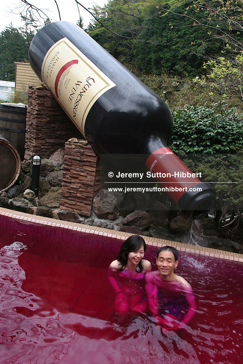 "A couple bathe in the ""red wine"" bath, ( a bath containing real red wine), at Hakone Kowakien  Yunessun in Tokyo, Japan, on Wednesday, Apr. 26, 2006. The huge wine bottle is 3.6m tall. Bathing in wine is a rejuvenation treatment for the body, and it has been said that the Queen of Egypt, Cleopatra loved to bath in wine. There are regular performances of pouring real wine into the spa a few times a day."