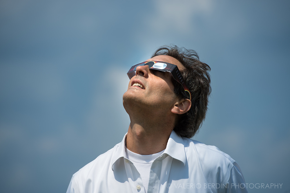A man staring at the eclipse, under the unique light of a darkened sky